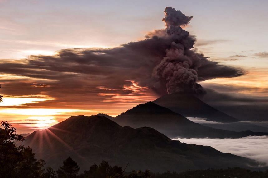 Mount Agung spewing smoke and ash yesterday. The volcano has been rumbling since September, forcing tens of thousands of people to flee to shelters. It began a series of mild eruptions last week.