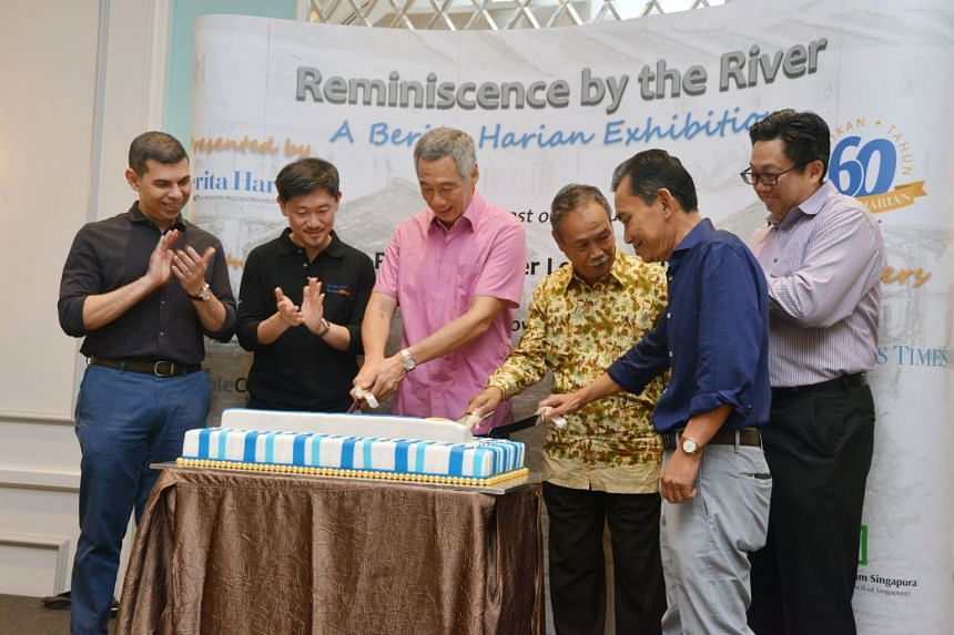 Prime Minister Lee Hsien Loong cutting the cake at yesterday's event to mark Berita Harian's 60th anniversary. With him are (from left) ST editor and editor-in-chief of SPH's English/Malay/Tamil Media Group Warren Fernandez; SPH deputy chief ex