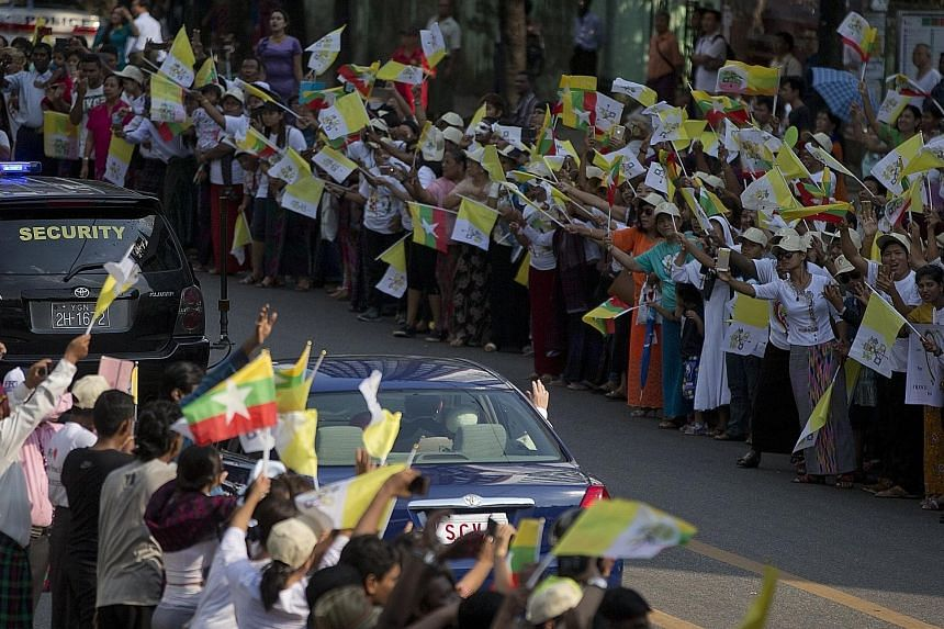 Above: A girl dressed in traditional dress embracing Pope Francis on his arrival. Left: The Pope waving from his car window at crowds gathered in Yangon. Thousands travelled across the country to see him.