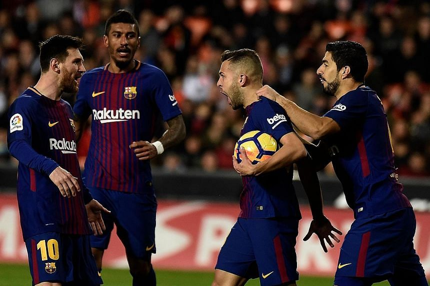 Barcelona left-back Jordi Alba (second from right) celebrating with team-mates Lionel Messi, Paulinho and Luis Suarezafter his 82nd-minute equaliser against former club Valencia on Sunday. The table-toppers maintained their four-point lead over the s