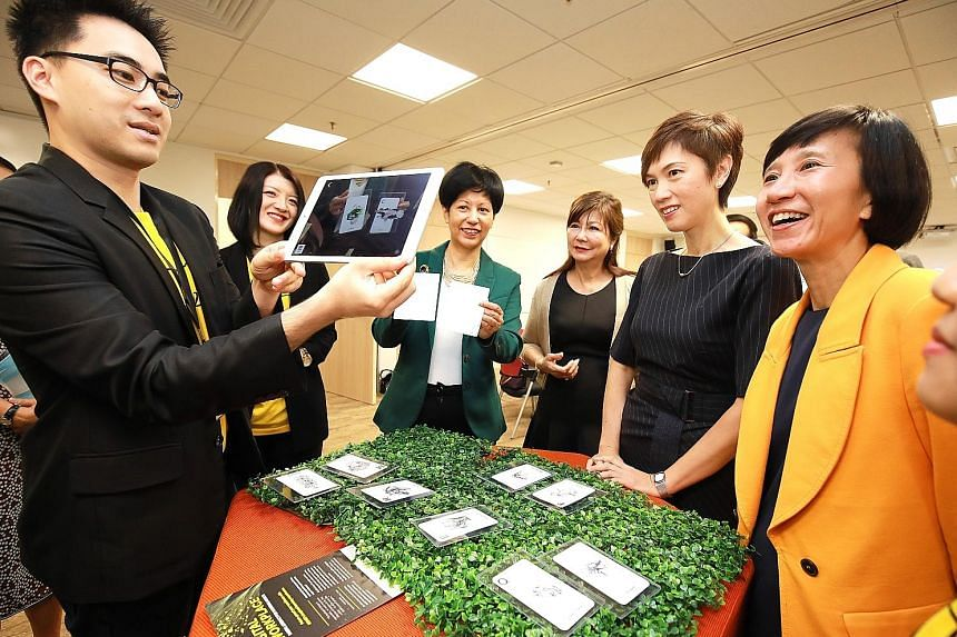Ms Josephine Teo (second from right) and Ms Indranee Rajah (third from left) watching a demonstration of augmented reality technology, which is part of the Professional Conversion Programme, together with United Overseas Bank's head of group human re