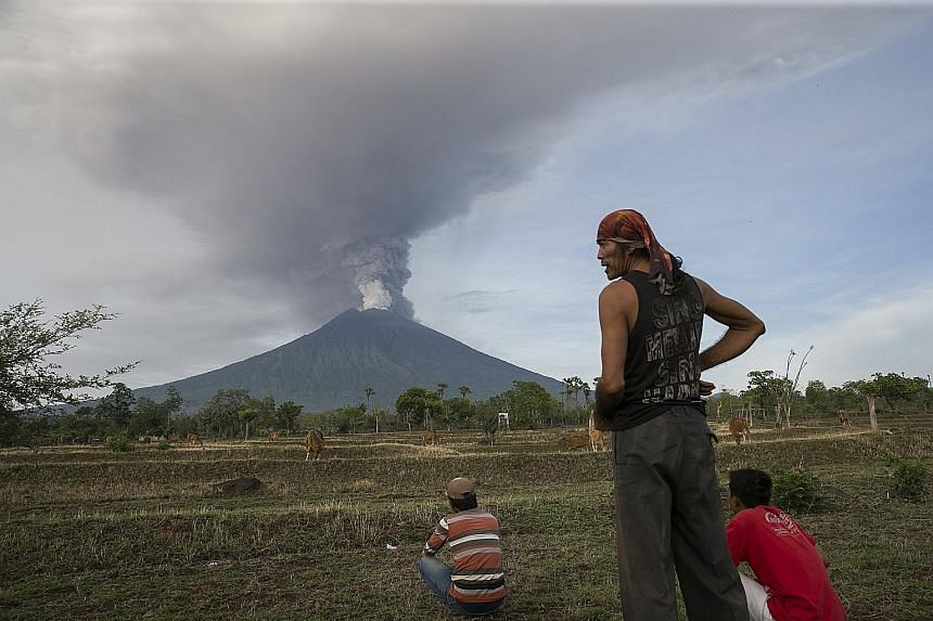 Mount Agung spewing thick ash into the sky, as seen from Datah, Karangasem, in Bali, yesterday. The disaster management agency urged all remaining villagers in the 8km to 10km danger zone to leave. The closure of Ngurah Rai airport could last longer