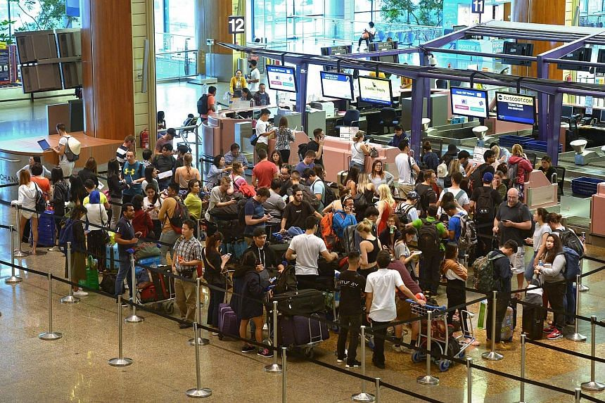 Left: Panels at Changi Airport's T4 informing passengers of cancelled flights to Bali yesterday. Right: At T2, Bali-bound travellers queued to rebook flights and switch destinations.