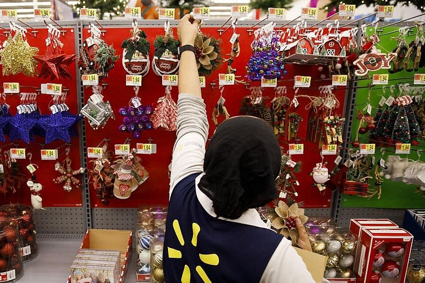 A Wal-Mart employee stocking Christmas ornaments at a store in Burbank, California, on Nov 16, ahead of the US holiday shopping season. The retailer has aggressively invested in making its prices more competitive against brick-and-mortar rivals since
