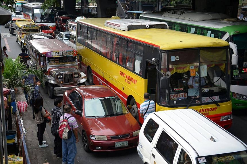 Commuters waiting for their ride along a main road in Manila.