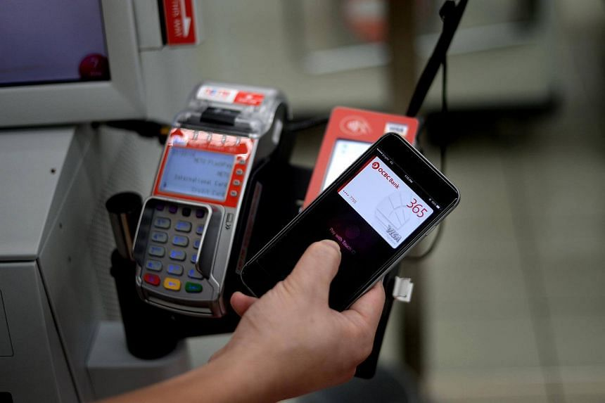 A customer using Apple Pay to pay at the self checkout counter. Usage of mobile wallets to make credit card payments here has jumped 53 per cent.