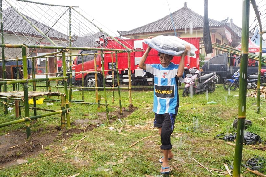 An evacuee at the evacuation shelter in Rendang after collecting a tarpaulin cover for his tent. As of Nov 27, at least half of the tents at the shelter did not have tarpaulin covers for their tents and many families were drenched when it rained.