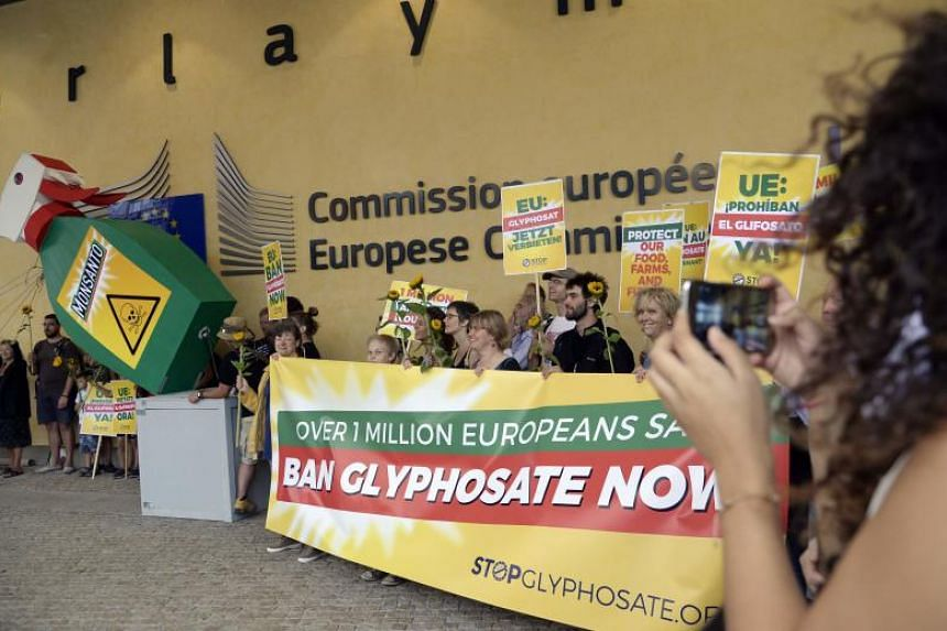 Activists pulling down a giant bottle of weedkiller as they demonstrate in favour of a Glyphosate ban by the European Union in front of the European Union Commission headquarter in Brussels on July 19, 2017.