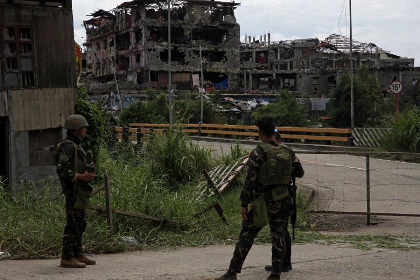 Soldiers stand on guard and look at damaged buildings and houses after government troops cleared the area from pro-Islamic State militant groups inside the war-torn area in Saduc proper, Marawi city, southern Philippines on Oct 22, 2017.
