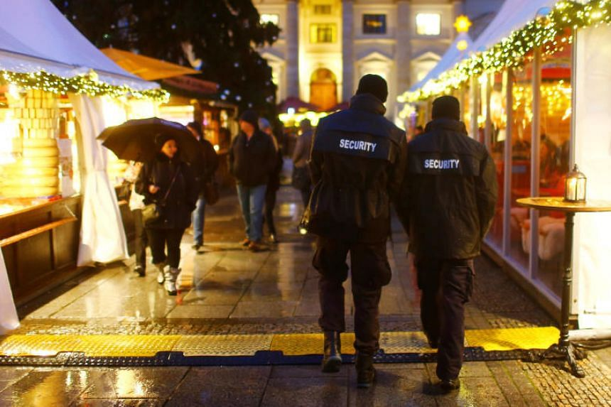 Security guards walk over the Christmas market at Gendarmenmarkt square in Berlin, Germany, on Nov 27, 2017.