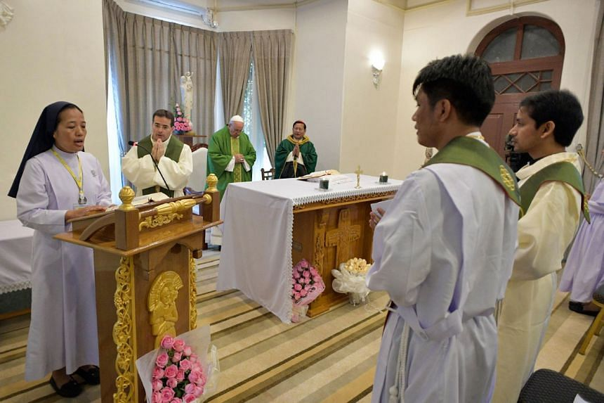 Pope Francis attending a private mass with Cardinal Charles Maung Bo (centre right), Archibishop of Yangon, in Yangon.
