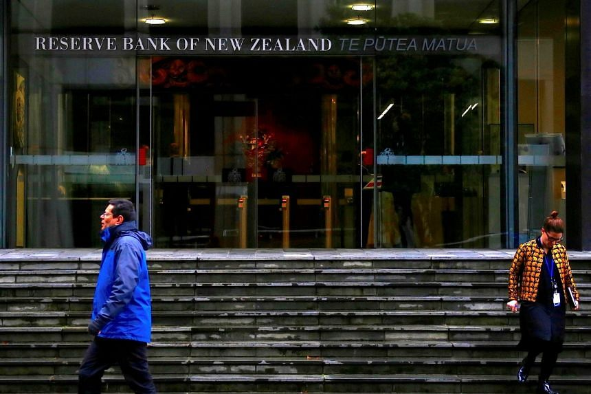 Pedestrians walk near the main entrance to the Reserve Bank of New Zealand located in central Wellington, New Zealand, on July 3, 2017.