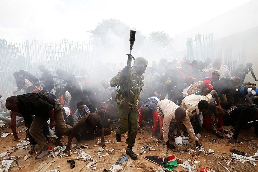 A police officer firing tear gas to control a crowd trying to force their way into a stadium yesterday to attend the inauguration of President Uhuru Kenyatta at Kasarani Stadium in Nairobi, Kenya. Mr Kenyatta was sworn in for a second term at an inau