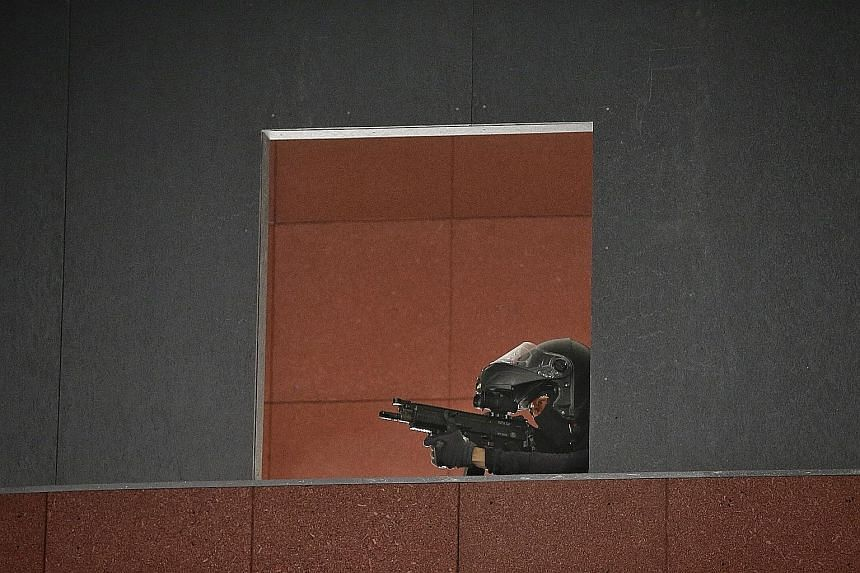 Reporter Tan Tam Mei preparing to fire the Heckler and Koch USP compact pistol at the Home Team Tactical Centre during a media tour on Monday. Armed Strike Team officers jumping out of a tactical response vehicle to handle a simulated threat. Above: