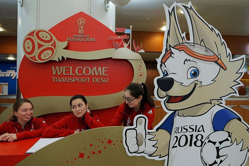 Staff await arrivals at the Sheremetyevo International Airport just outside Moscow for the World Cup Finals draw. Next to them is an ad board of Zabivaka, the competition's wolf mascot.