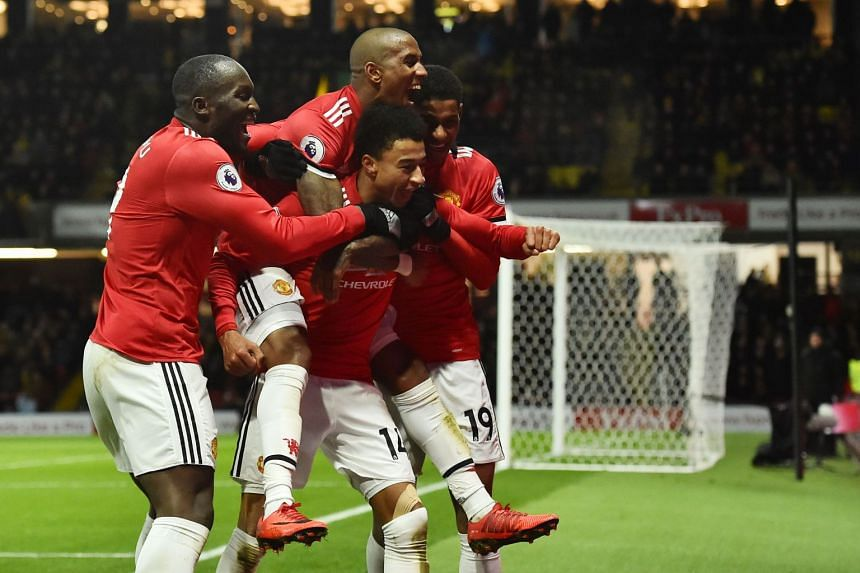 Manchester United's English midfielder Jesse Lingard (centre) celebrates with team mates after scoring their fourth goal.