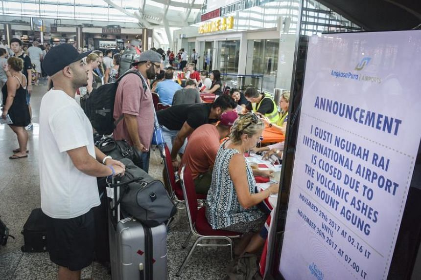 Stranded tourists listen to airport officials following the volcanic eruption of Mount Agung at Ngurah Rai international Airport in Denpasar, Bali, Indonesia, on Nov 29, 2017.