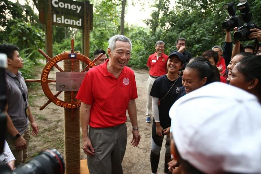 Prime Minister Lee Hsien Loong unveils a commemorative OBS ships wheel on Coney Island.