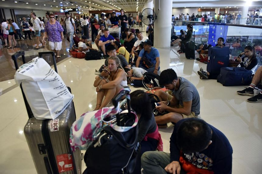Passengers gather at the Gusti Ngurah Rai International airport in Denpasar, Bali on Nov 27, 2017, after flights were cancelled due to the threat of an eruption by the Mount Agung volcano.