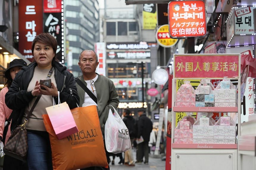Foreign tourists walk past shops bearing Chinese signs in Seoul's Myeongdong shopping area, one of the top tourist spots in South Korea on Nov 28, 2017.