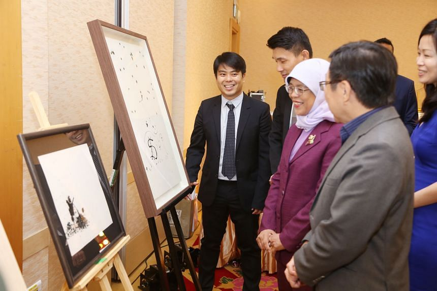 President Halimah Yacob, Parliamentary Secretary for Culture, Community and Youth Baey Yam Keng (second from far left), former minister Mah Bow Tan (in grey jacket), and Tampines GRC MP Cheng Li Hui looking at two paintings yesterday by Raffles Fine