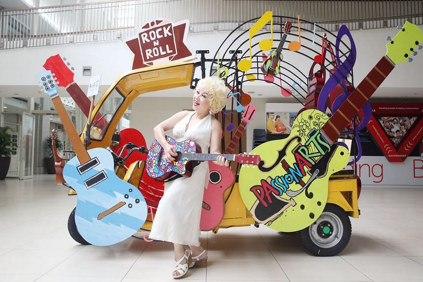 Above: Ms Susan Teo, 64, a volunteer leader with the PAssionArts guitar contingent, dressed up as 1950s American celebrity Marilyn Monroe in front of an e-trishaw. Left: Robots dancing along with performers during a media preview yesterday. There wil