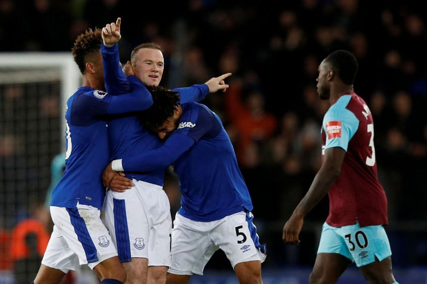 Everton's Wayne Rooney celebrates scoring their third goal to complete his hat-trick.