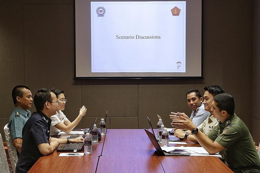 Representatives from the SAF and Indonesian armed forces, as well as the Singapore Police Force, taking part in a discussion at Sheraton Towers yesterday during the inaugural SAF-TNI Counter-Terrorism Table-Top Exercise. A concern of both sides was f