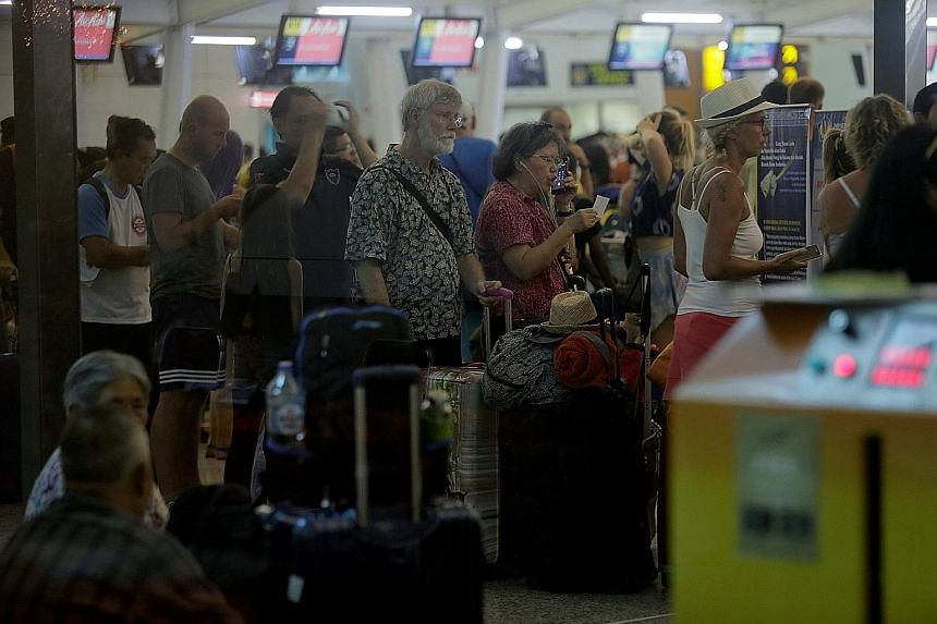 Passengers queueing at a check-in counter after Bali's Ngurah Rai International Airport reopened yesterday. Officials cautioned that the airport could close again depending on the wind direction.
