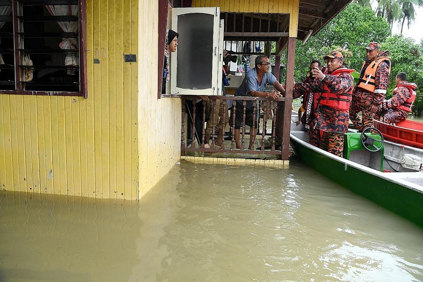 Kelantan's Fire and Rescue Department director Nazili Mohmood (third from right) giving advice to flood victim Nasir Ahmad, 68, while visiting flood-hit areas in Kampung Siput, Meranti, yesterday. The state has at least 8,000 people seeking shelter i