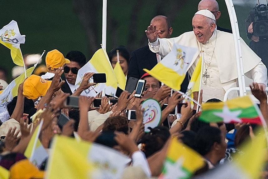Above: Pope Francis waving to well-wishers as he moves through the estimated 150,000 faithful in his popemobile. Worshippers held Myanmar flags and wore colourful costumes from the country's myriad ethnic groups. Right: Nuns taking photos before the