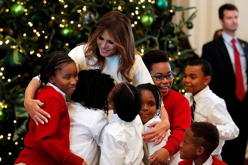 Mrs Melania Trump hugging schoolchildren at the White House on Monday. A report in Vanity Fair said that she was unprepared and had not wanted the role of First Lady.