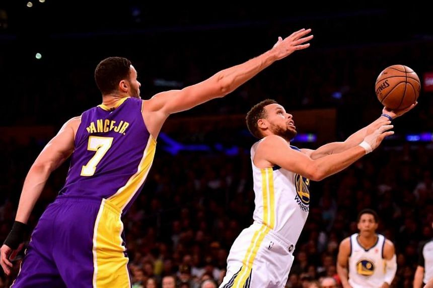 2e0d90c5d863 Golden State Warriors guard Stephen Curry scoring a layup against Los  Angeles Lakers forward Larry Nance