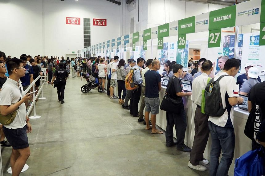 Participants queue up to collect their race packs at the Standard Chartered Singapore Marathon Race Expo at Marina Bay Sands on Nov 30, 2017.