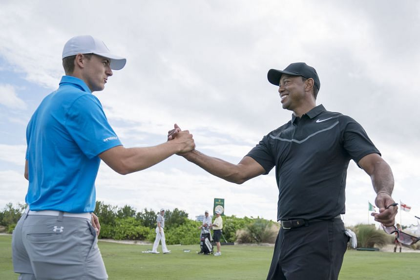 "Jordan Spieth shaking hands with Tiger Woods during a practice round before the Hero World Challenge tournament in the Bahamas. Woods says he is ""loving life"" because he is free of pain."