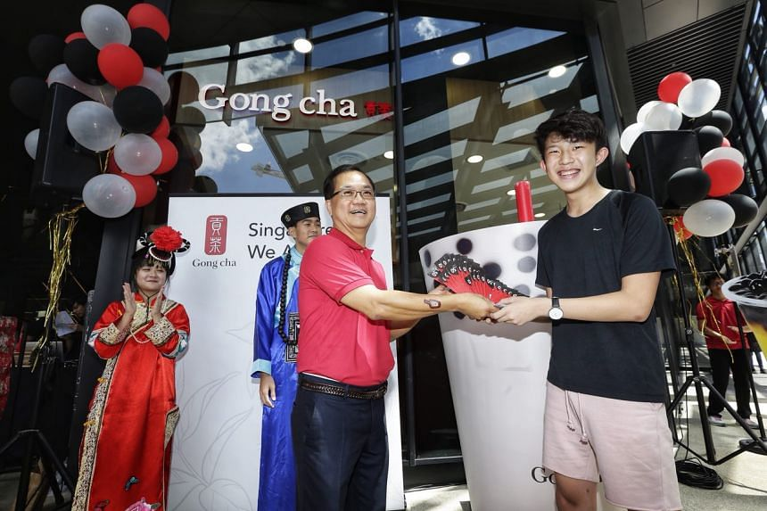 Gong Cha Singapore chief executive Kang Puay Seng handing vouchers, which can be used to redeem 99 cups, to student Daryl Yoon, who was the first person in the queue.
