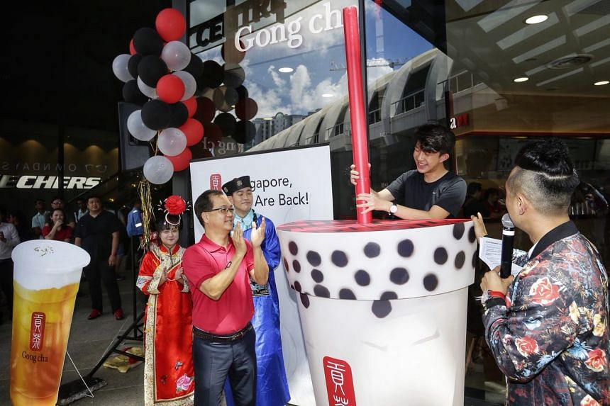 Gong Cha Singapore chief executive Kang Puay Seng claps as student Daryl Yoon inserts a huge straw into a cup to launch Gong Cha at Singpost Centre on Dec 1, 2017.