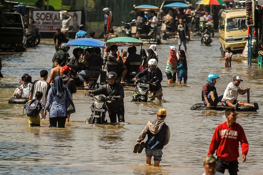 People wading through floods caused by heavy seasonal rain last month in Bandung, Indonesia.
