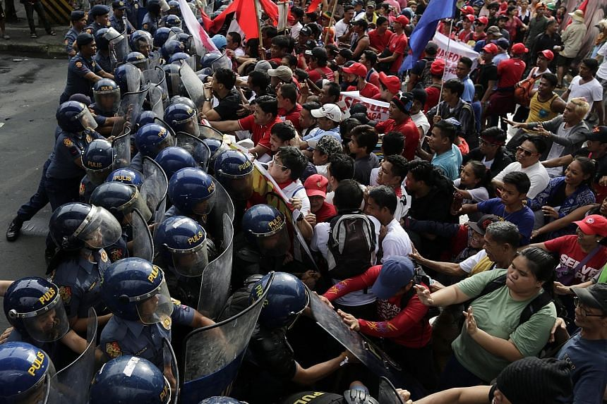 Filipinos scuffling with anti-riot police during a protest against President Rodrigo Duterte protest in Manila yesterday. According to news reports, thousands of critics of Mr Duterte staged rallies to denounce his plan to set up a revolutionary gove