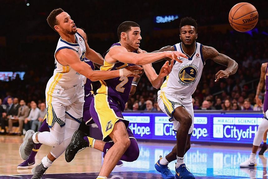 Lonzo Ball of the Los Angeles Lakers loses the ball as he drives to the basket between Stephen Curry (far left) and Jordan Bell of the Golden State Warriors. Despite a slow start, Curry scored 13 of his 28 points in overtime to lead his team to a 127