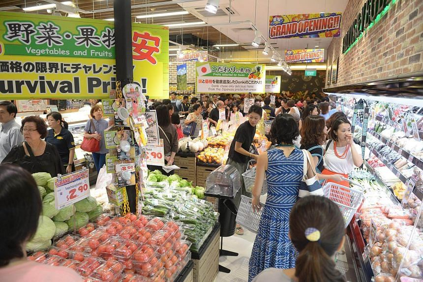 The first customers enter the Japanese discount chain Don Don Donki as it opens at the Orchard Central on Dec 1, 2017.