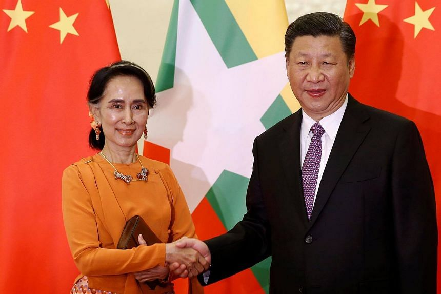Myanmar State Counsellor Aung San Suu Kyi shakes hands with Chinese President Xi Jinping as they meet at the Great Hall of the People in Beijing, on May 16, 2017.
