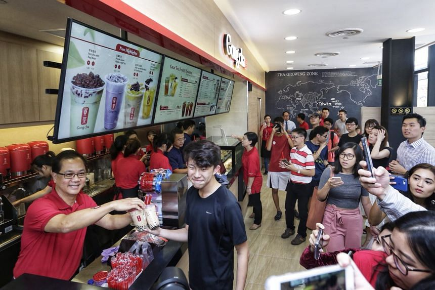 Gong Cha Singapore chief executive Kang Puay Seng serves the first cups of bubble tea to student Daryl Yoon, who was the first person in the queue.