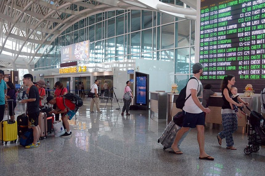 Passengers wait for their flight schedule at the Ngurah Rai International Airport in Bali, on Nov 26. Jetstar will cancel nine of 15 planned flights out of Bali following a volcanic ash forecast on Dec 1.