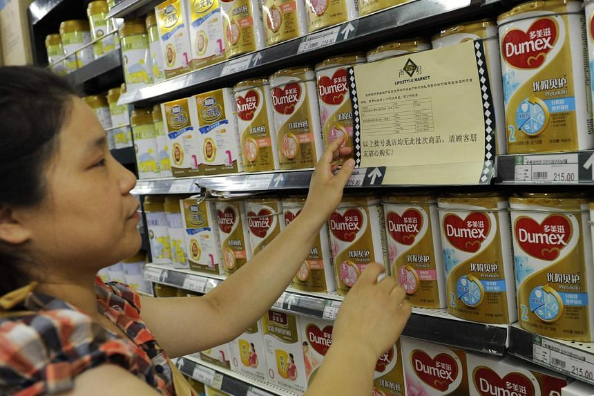 A woman checking a guarantee announcement on a shelf of baby formula, which uses the New Zealand dairy company Fonterra as its raw material supplier.