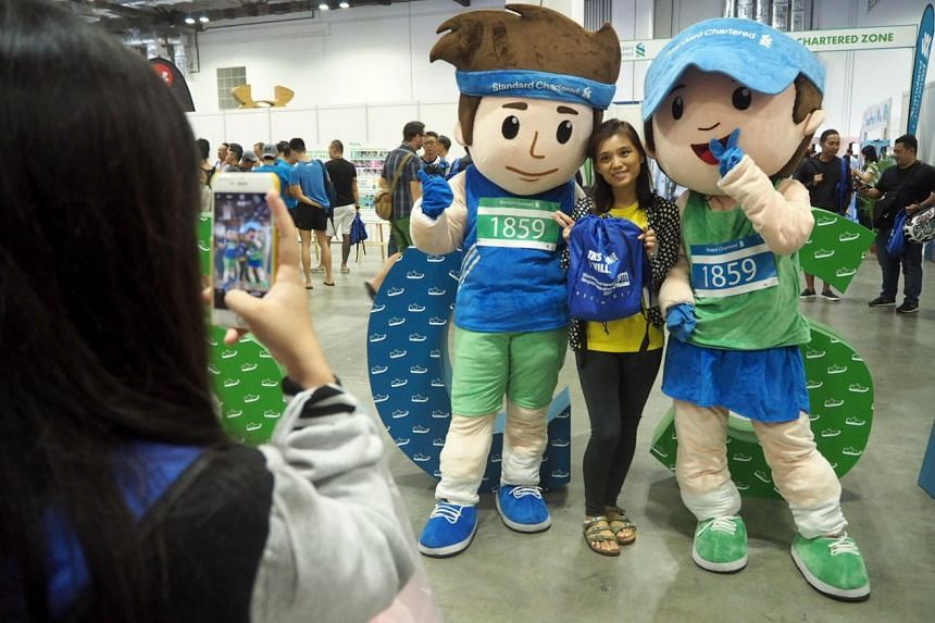 A participant posing for a photo with mascots at the Standard Chartered Singapore Marathon Race Expo at Marina Bay Sands on Nov 30, 2017.