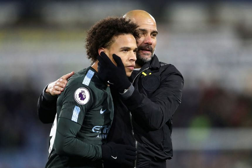Manchester City manager Pep Guardiola and Leroy Sane celebrate after beating Huddersfield.
