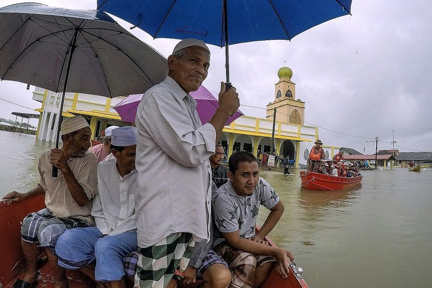 Villagers making their way to a mosque for Friday prayers after flood waters submerged the mosque compound in Kelantan yesterday.