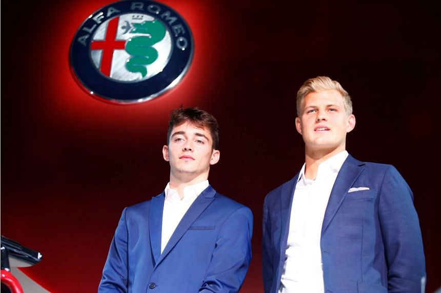 Formula One drivers Charles Leclerc of Monaco (left) and Marcus Ericcson of Sweden pose next to the Alfa Romeo Sauber Formula One car during a presentation in Arese, Italy on Dec 2, 2017.