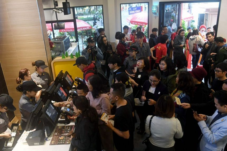 People queue up to order food at Hanoi's first McDonald's fast food chain restaurant on Dec 2, 2017.